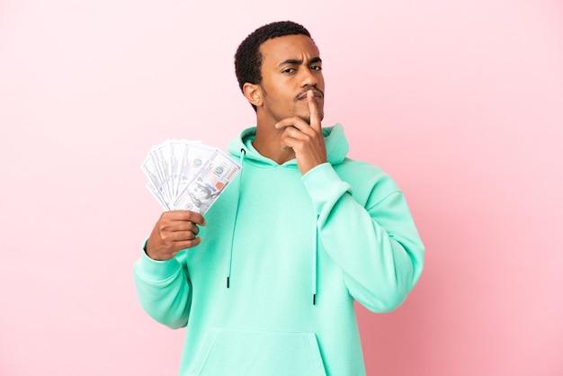 Молодой человек берет много денег на изолированном розовом фоне, сомневаясь, глядя вверх