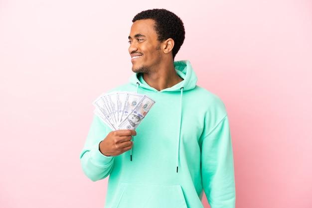 Молодой человек берет много денег на изолированном розовом фоне, глядя в сторону