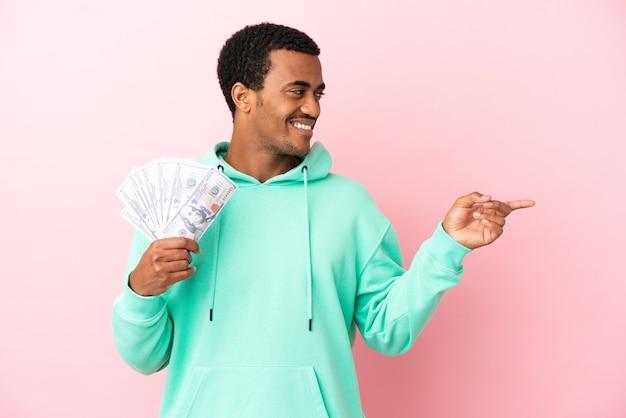 Молодой человек берет много денег на изолированном розовом фоне, указывая пальцем в сторону и представляет продукт