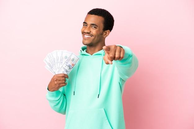 Молодой человек берет много денег на изолированном розовом фоне, указывая вперед со счастливым выражением лица