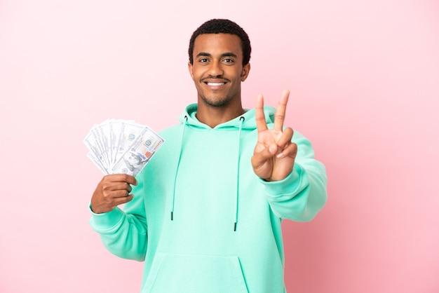 Молодой человек берет много денег на изолированном розовом фоне, улыбаясь и показывая знак победы Premium Фотографии