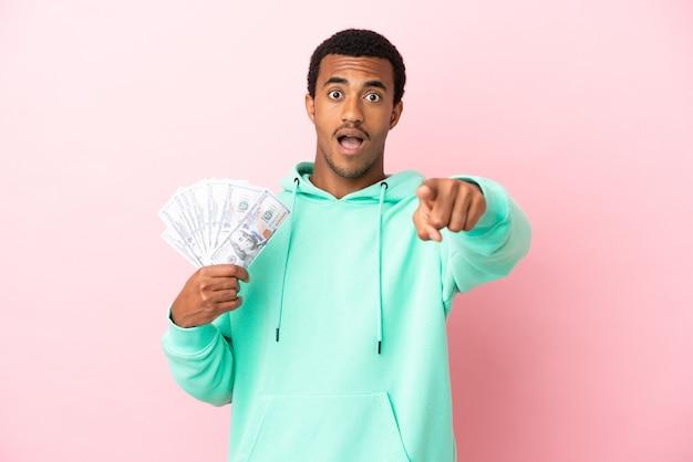 Молодой человек берет много денег на изолированном розовом фоне, удивлен и указывая вперед