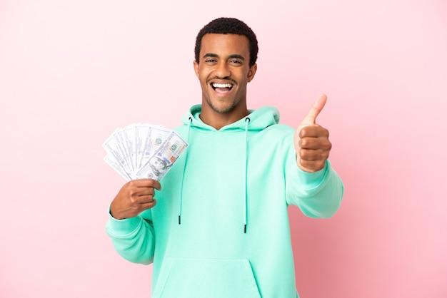 Молодой человек берет много денег на изолированном розовом фоне с большими пальцами руки вверх, потому что произошло что-то хорошее