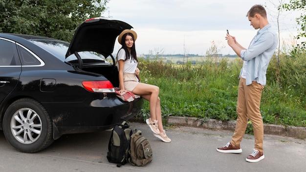 Молодой человек фотографирует свою девушку в отпуске
