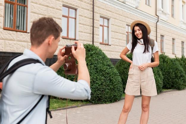 彼のガールフレンドの写真を撮る若い男