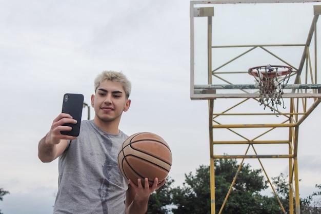 放棄されたバスケットボールコートで自分撮りをしている若い男。