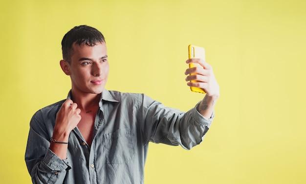 Молодой человек делает селфи со своим мобильным телефоном на желтом фоне
