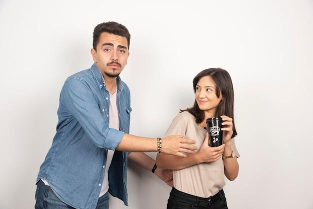 若い男が女の子から一杯のコーヒーを奪う。