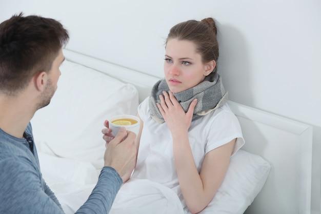 自宅のベッドに座っている病気の女性の世話をする若い男
