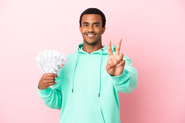 Young man taking a lot of money over isolated pink background smiling and showing victory sign