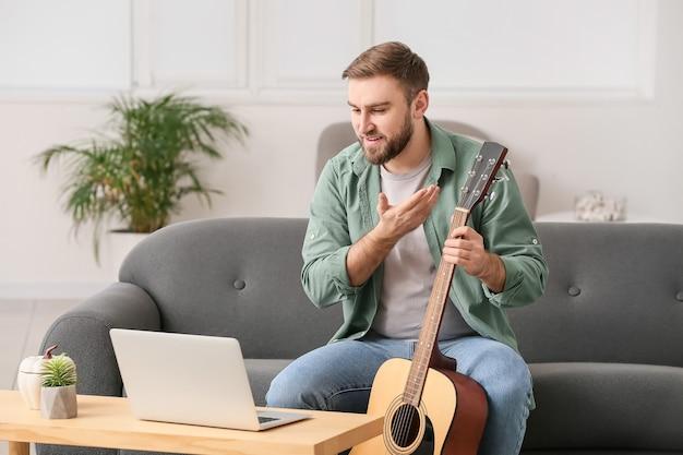 Молодой человек берет уроки музыки онлайн дома