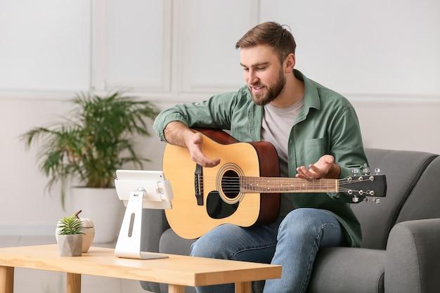 집에서 온라인 음악 수업을받는 젊은 남자