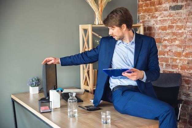 Молодой человек делает заметки о повседневных задачах, сидя на столе