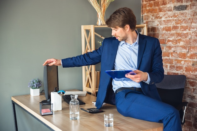 Young man taking notes daily tasks sitting on table