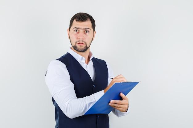 シャツとベストのクリップボードにメモを取り、集中して見える若い男