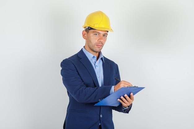 Молодой человек делает заметки в буфере обмена в костюме, защитном шлеме и выглядит занятым