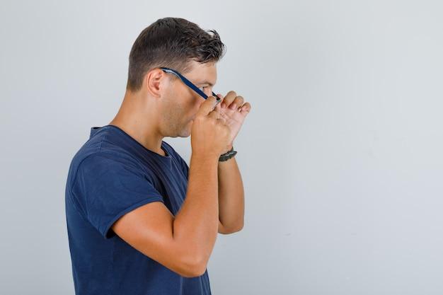 진한 파란색 티셔츠에 안경을 벗고 피곤 찾고 젊은 남자.