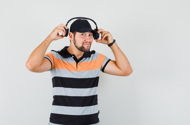 헤드폰을 벗고 t- 셔츠, 모자에 웃 고 젊은 남자