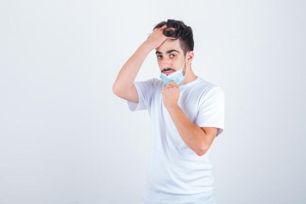 Молодой человек снимает маску, расчесывает волосы рукой в белой футболке и выглядит уверенно