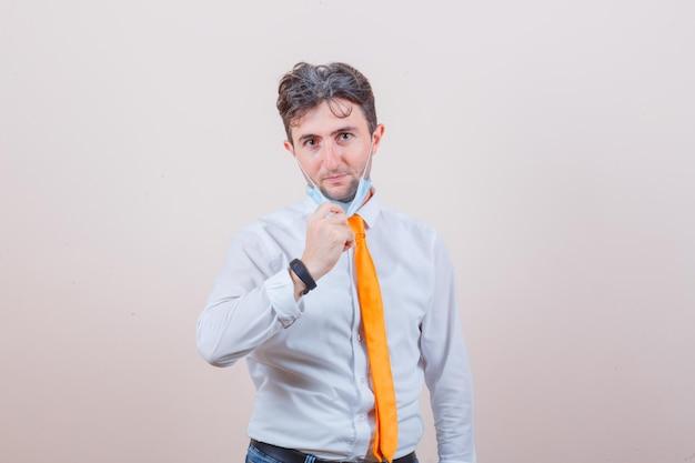 Молодой человек снимает медицинскую маску в белой рубашке, галстуке и выглядит позитивно