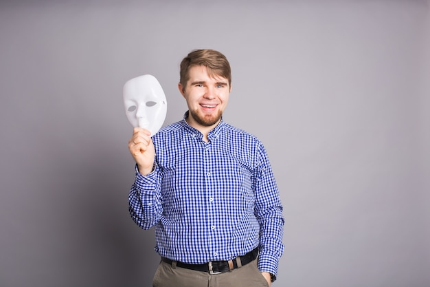 Young man taking off plain white mask revealing face, gray wall