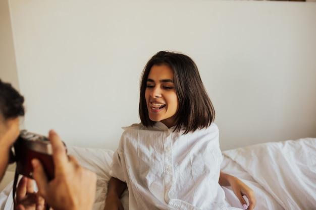 寝室で彼の美しいガールフレンドの写真を撮る若い男。