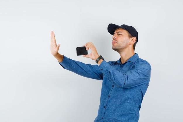 青いシャツ、キャップ、正面図で携帯電話で誰かの写真を撮る若い男。