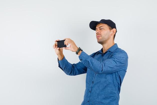 青いシャツ、キャップ正面図で携帯電話で写真を撮る若い男。