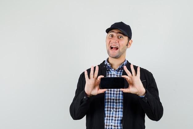 Молодой человек фотографирует на мобильном телефоне в рубашке, куртке, кепке и выглядит весело. передний план.