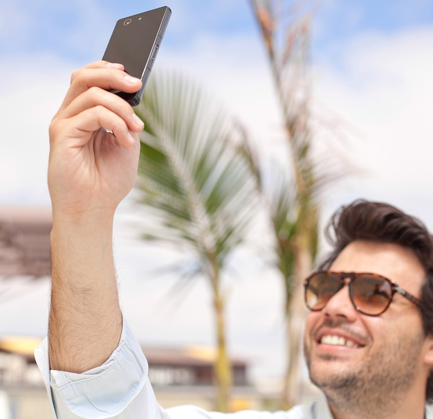 Young man taking a photo with his mobile phone