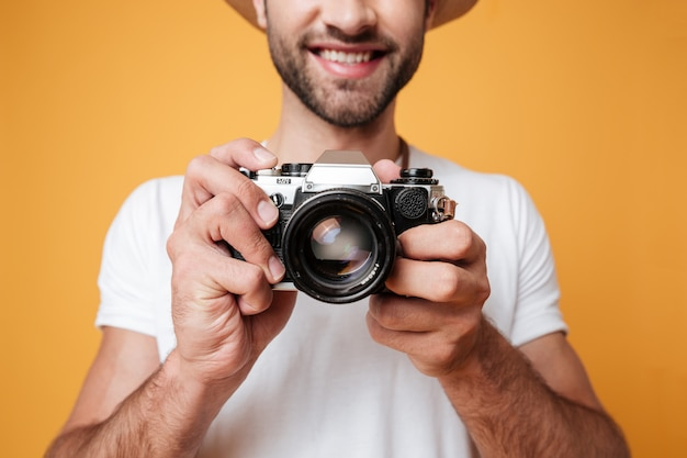 Young man taking photo with retro camera
