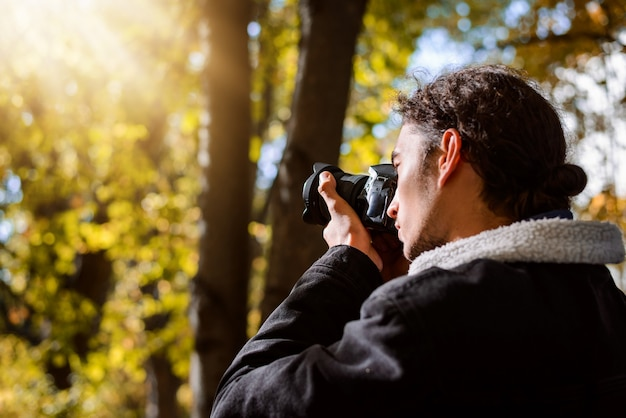 Young man taking pictures in the autumn park