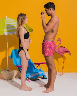 Young man taking pictures of girlfriend in bikini in studio