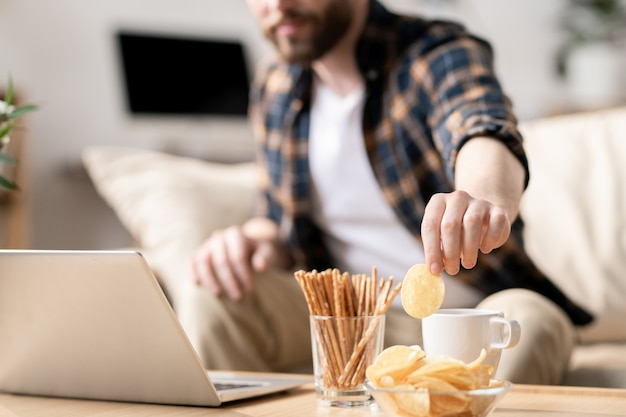 Young man taking potato chip out of glass bowl while sitting on sofa in front of laptop on table and having snack