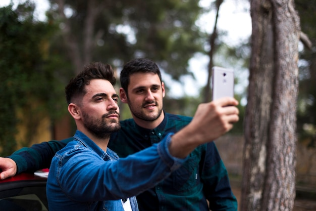 Young man taking selfie on mobile phone with his friend