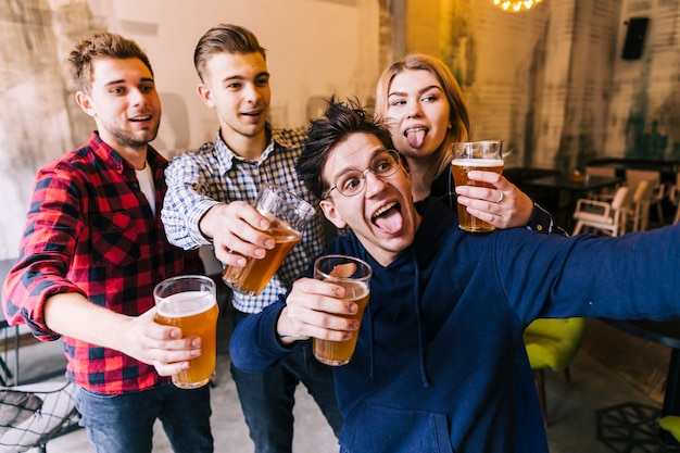 Young man taking selfie on mobile phone with his friends holding the glasses of beer