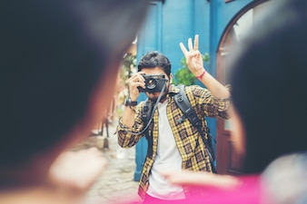 Young man taking selfie of his friends while traveling in urban together.
