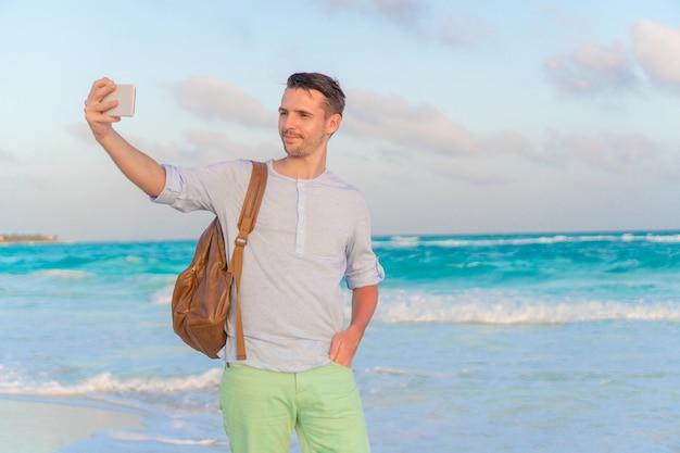 Молодой человек принимает selfie на пляже