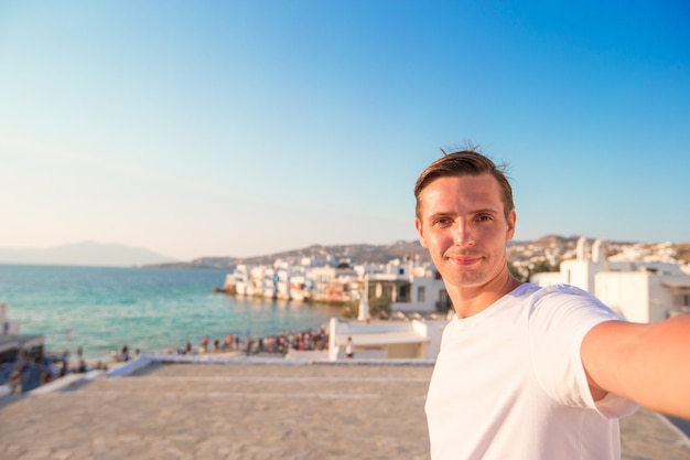 Young man taking selfie portrait in little venice in mykonos
