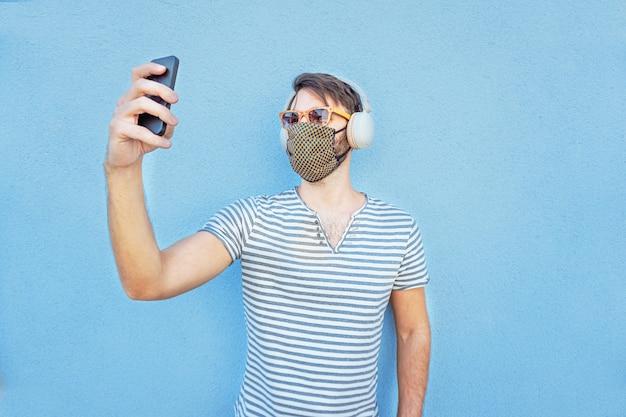 若い男がフェイスマスクでselfieを取る