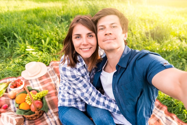 Young man taking selfie with girlfriend on plaid