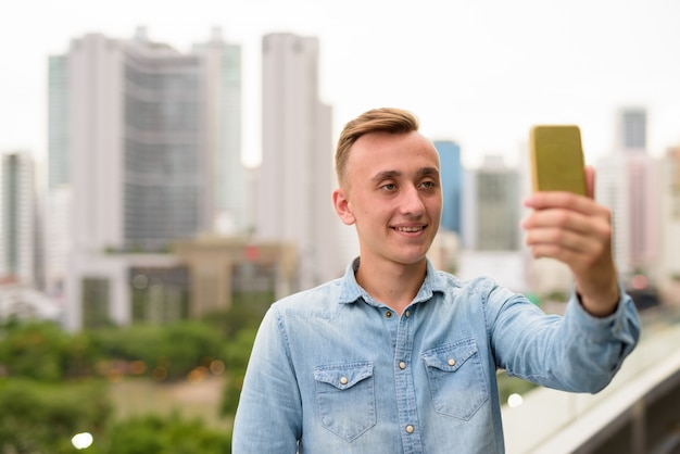 Young man taking selfie with mobile phone in city