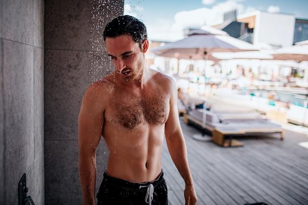 外でシャワーを浴びている若い男。水の手順を持っている強い筋肉と強力な男。ドロップダウン。体と頭を洗う。外で一人で。