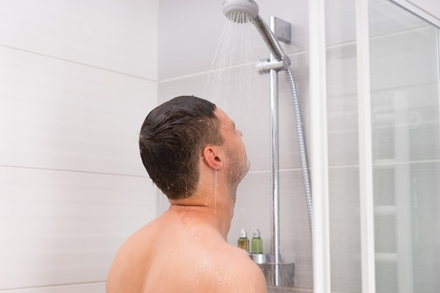 Young man taking a shower, standing under flowing water in shower cabin with transparent glass doors in the bathroom