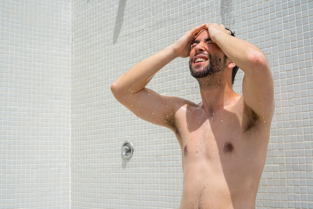 Young man taking a shower