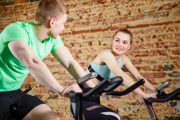 Young man talking to a cute blonde while they both do some cardio on a bicycle at the gym