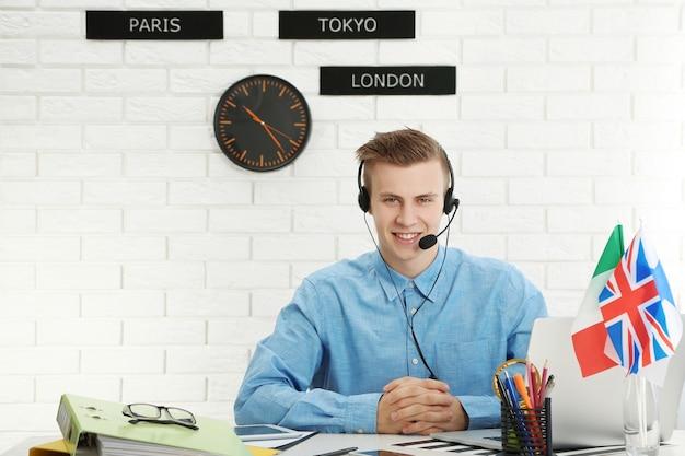 여행 회사의 사무실에서 헤드셋에 얘기하는 젊은 남자