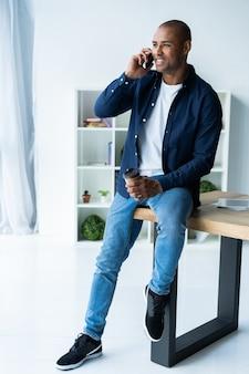 オフィスで彼の携帯電話で話している若い男。ノートパソコンを持って机に座っているアフリカの幹部