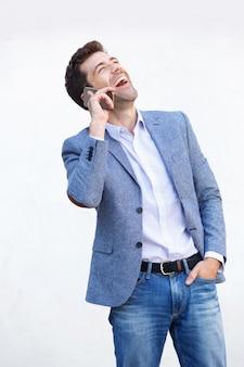 携帯電話で話して、白い背景で笑っている若い男
