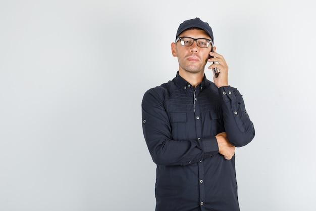 黒のシャツで携帯電話で話している若い男